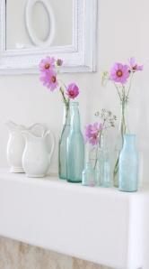 Een stilleven van verschillende flesjes met vrolijke bloemen